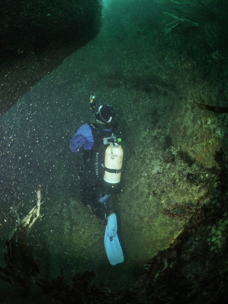 7.Diver holding a small underwater video camera and filming the remains on the seabed