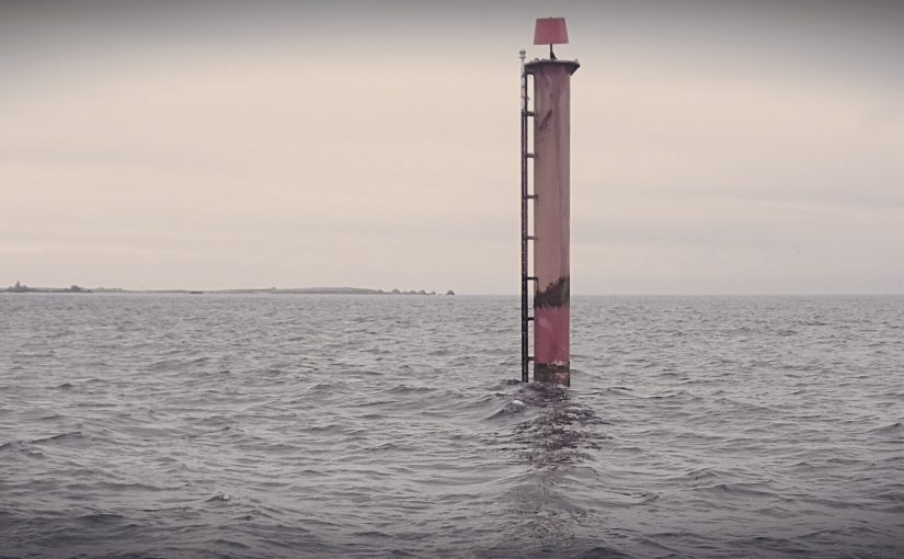 Seascape, calm sea occupies lower half of the image, light grey / pink upper half of image. Just off-centre to the right, a red cylindrical tower rises well out of the sea, which is the Trinity House beacon marking the beacon marking the wreck site.