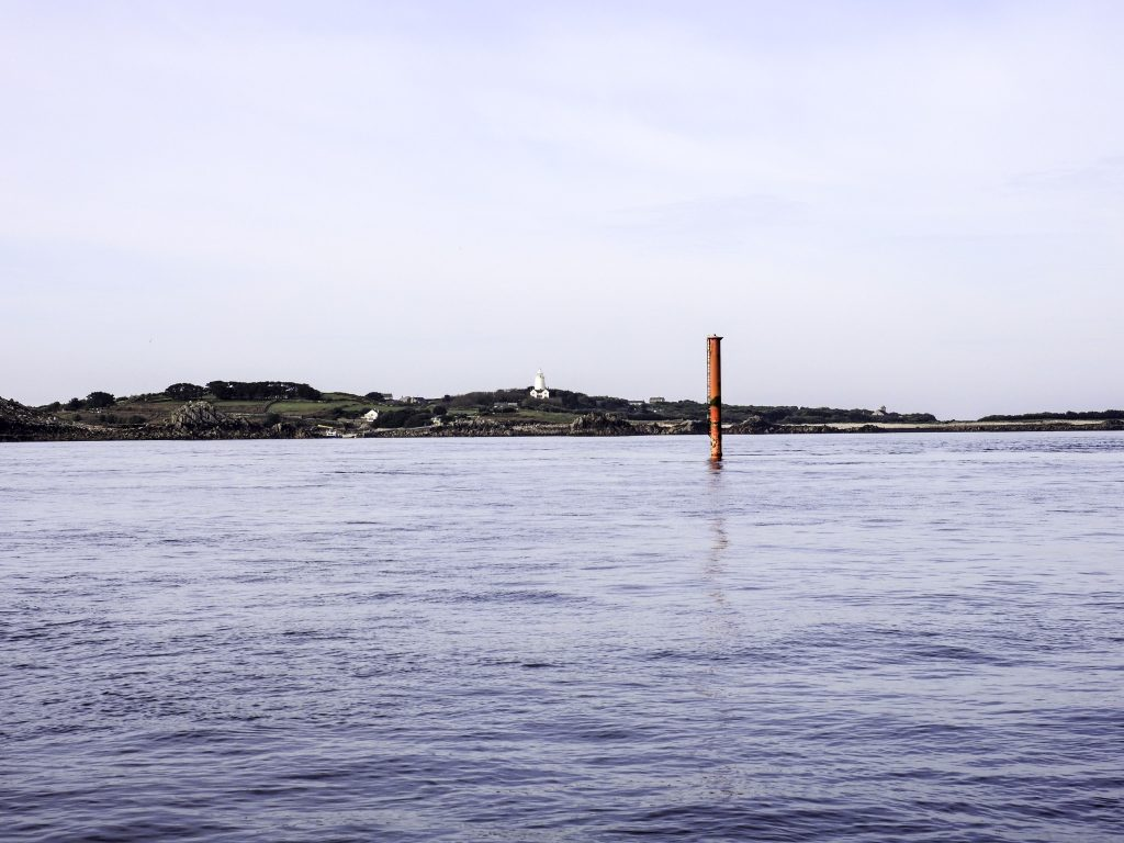 Metal pole rising from the sea surface. The island of St Agnes is visible in the background where the white painted lighthouse is visible