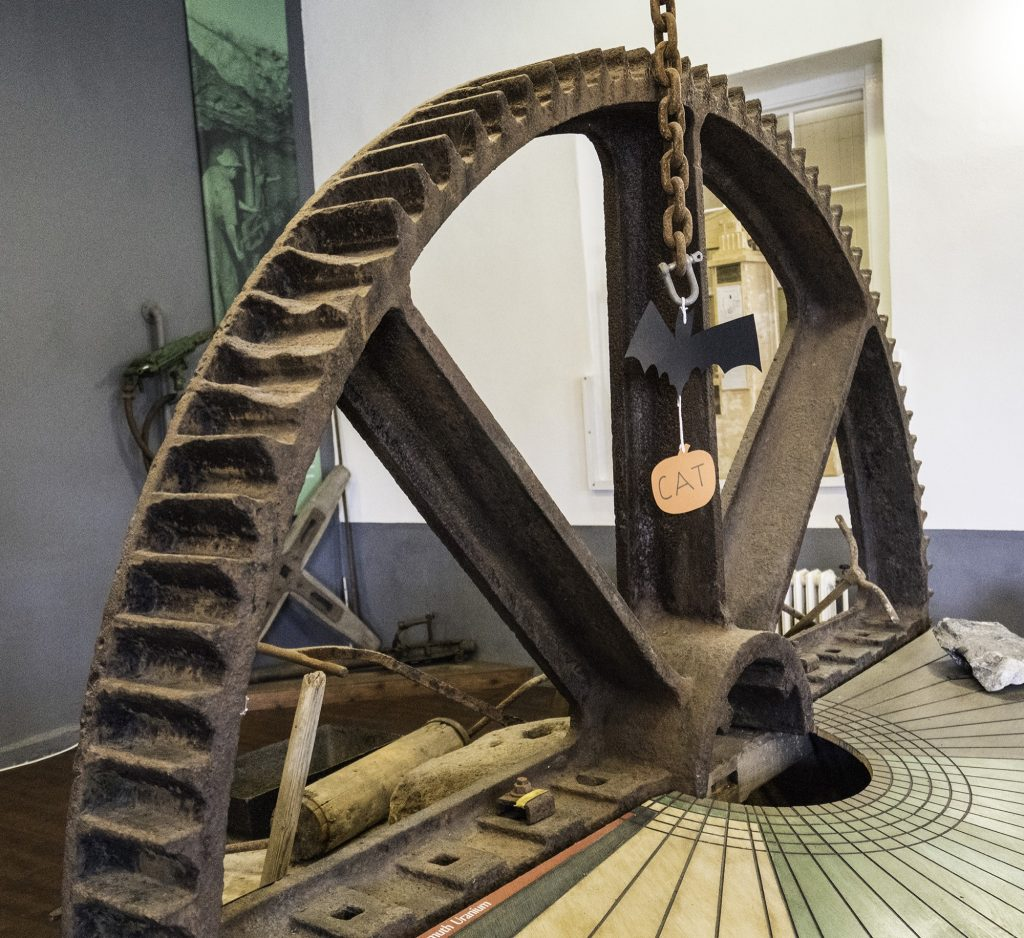Large iron wheel with gear teeth around the rim, on display at East Pool Mine in Cornwall