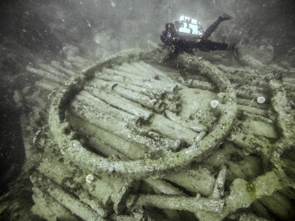A diver swimming over the large wheel at the centre of the cargo mound