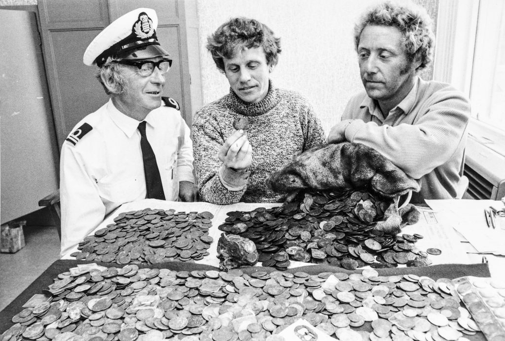 Three men sitting at a table which is covered with coins recovered from the site