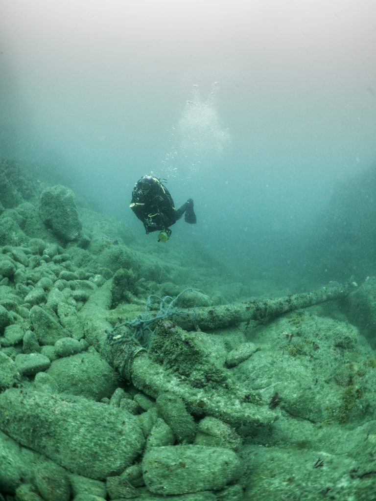 Large iron anchor sitting on a rocky seabed, with a diver swimming above