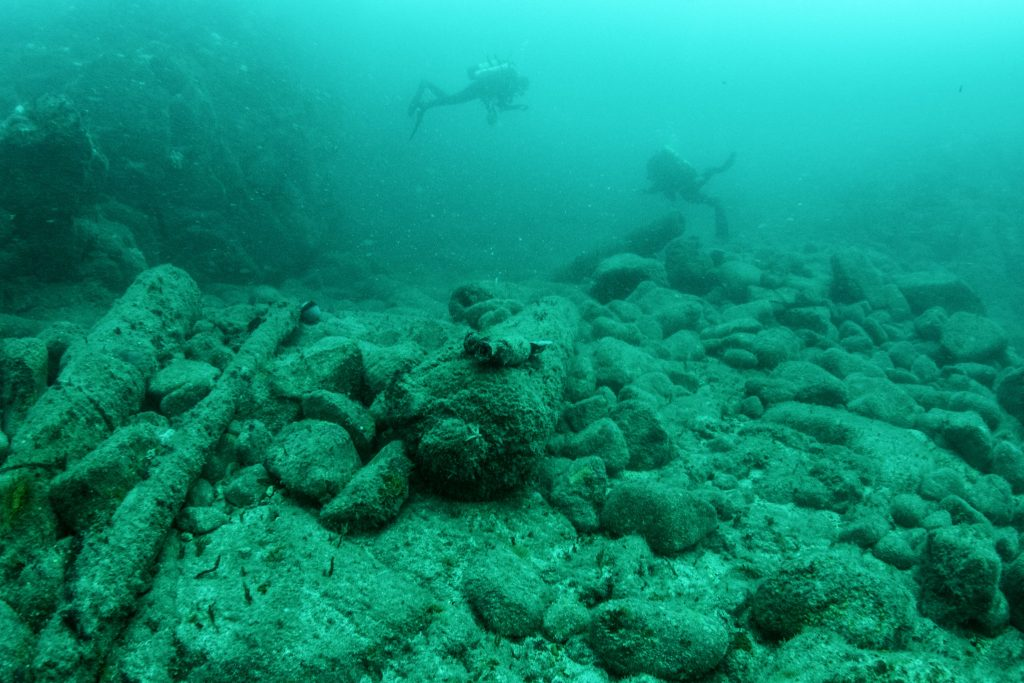 Number of iron cannons sitting on a rocky seabed, with two divers swimming above