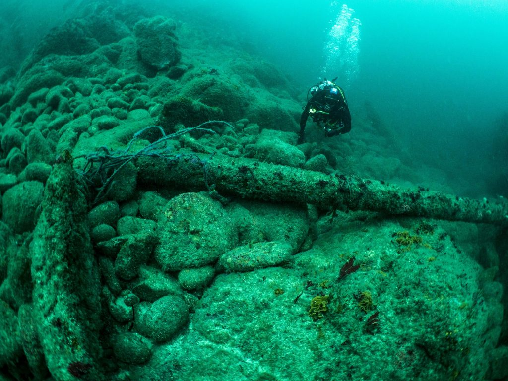 Large iron anchor sitting on a rocky seabed with a diver swimming nearby