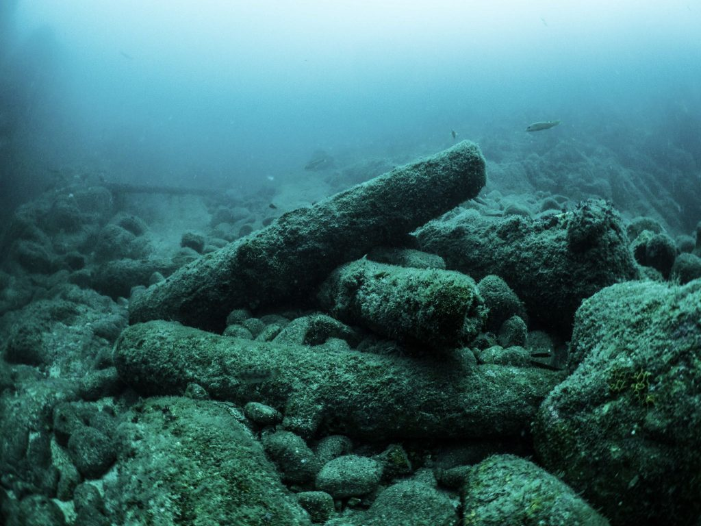 Group of iron cannon in a jumbled heap on a rocky seabed.