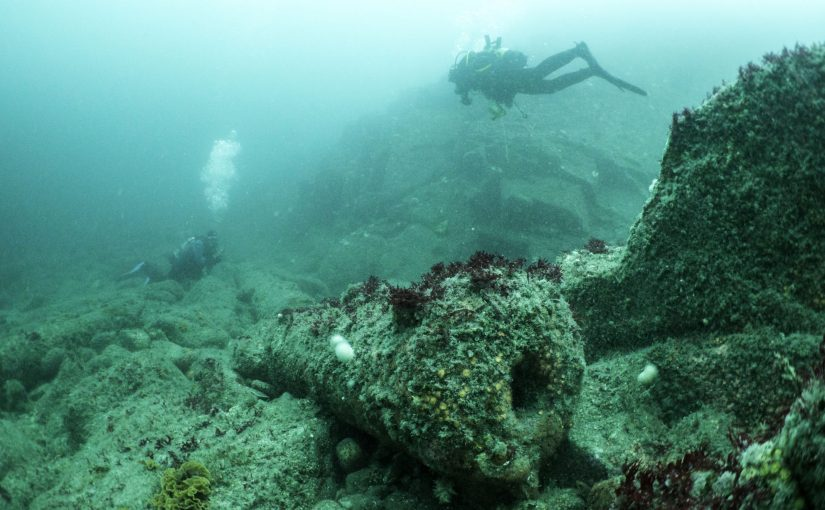 Cast iron cannon – muzzle facing the viewer – sitting on a boulder-strewn seabed with two divers swimming above