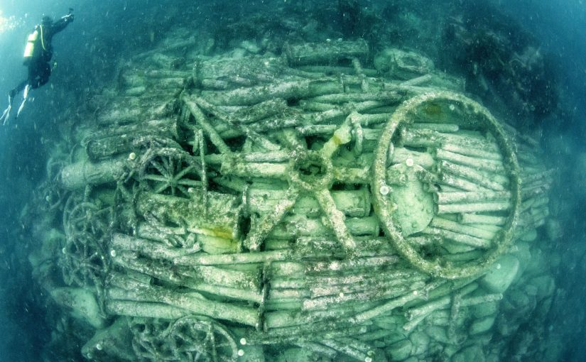 View from above of the cargo mound lying on the seabed, picked out in green. The cargo mound consists of iron pipes laid horizontally and wheels. The most prominent features are the six-spoked rimless wheel at the centre of the image and an empty circular wheel rim to its right.