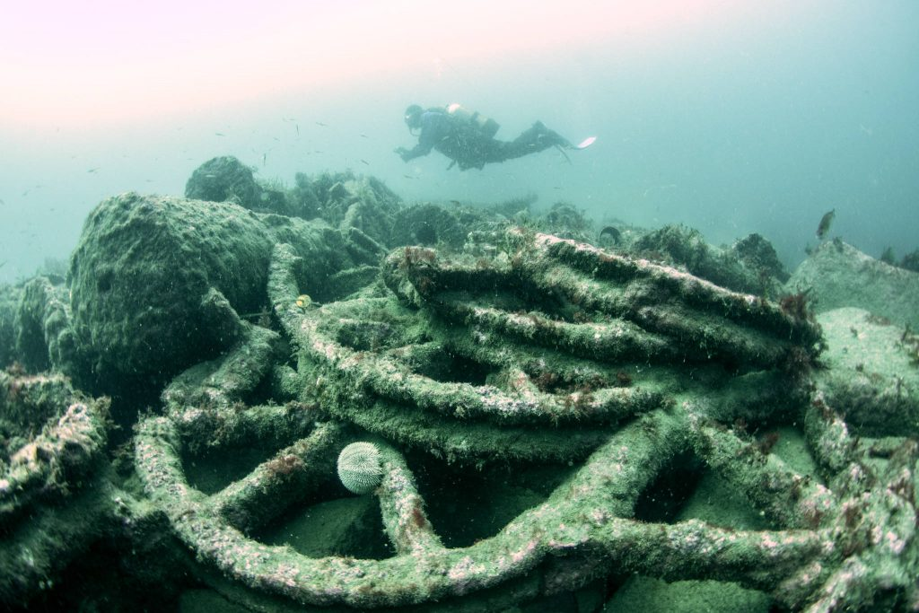 A diver swims over the pile of iron wheels on the seabed