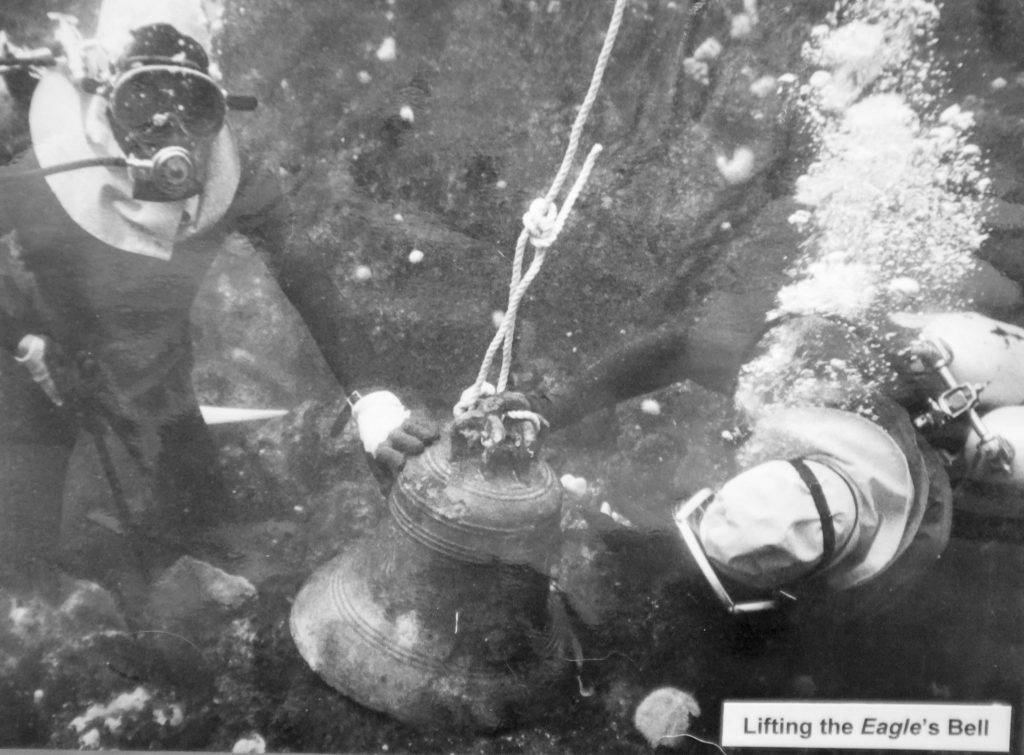 Black and white photograph showing two divers on the seabed, wearing light-coloured high visibility hoods. A ship's bell sits between them, with a rope attached ready to lift the bell to the surface