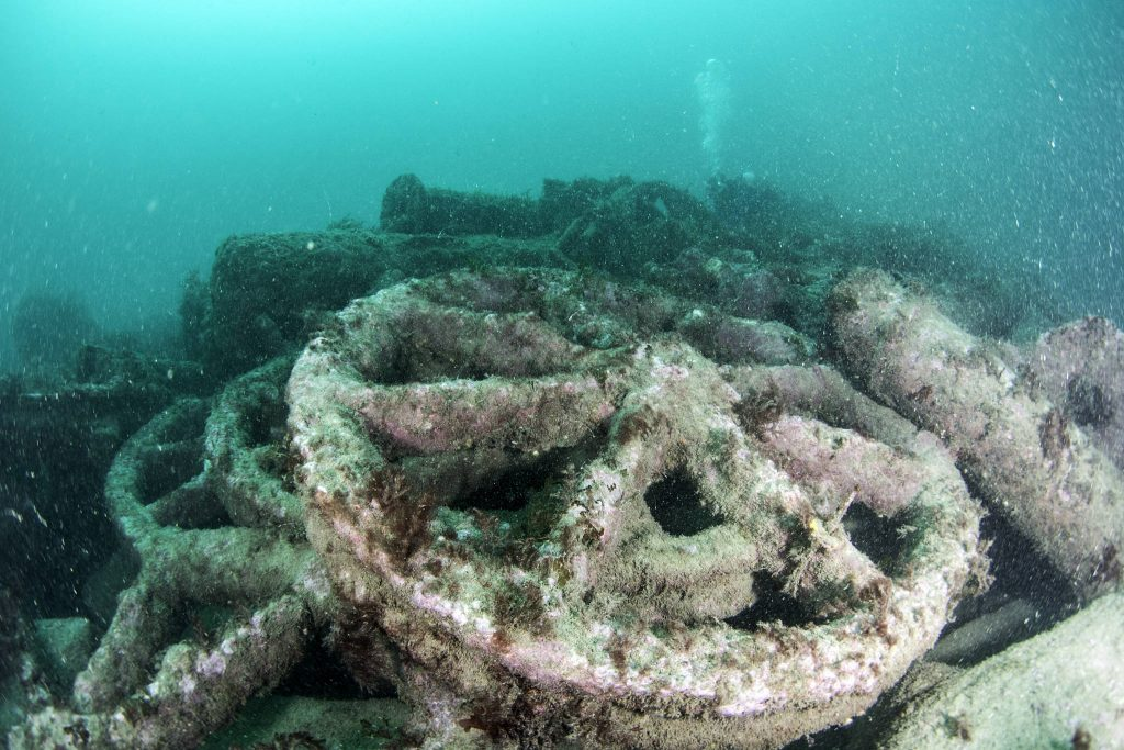 Six-spoked iron wheel sitting on top of several similar wheels on the seabed
