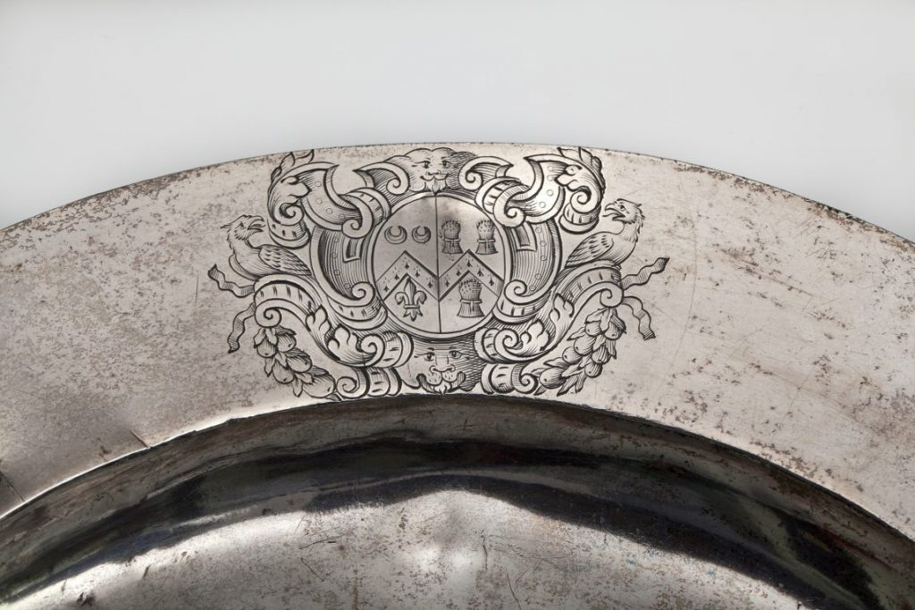 Detail of the silver plate showing a crest engraved on the rim