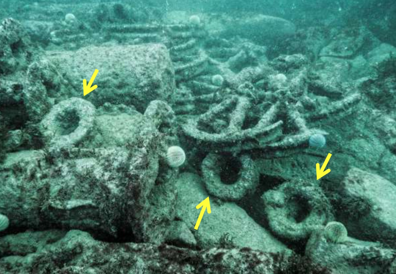 Photograph of broken wheels and circular iron collars on the seabed. The collars are marked with yellow arrows.